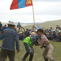 MONGOLIA. Nomadic herders wrestle at a naadam festival on a remote pass in Arbulag Sum, near Muren in Hovsgol Aimag, Mongolia. This ancient sport is immensely popular across the country, and is playfully practiced on a regular basis by many young men.