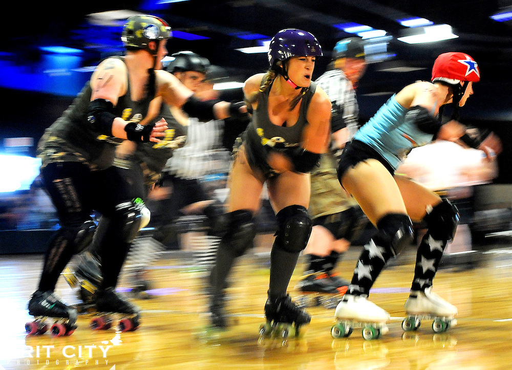 """G I Janes' Patty Jean King, center, or """"PJ Ruckus"""" winces as she tries to keep Bombshell Betties jammer Sarah Howard, right, aka """"Gloria Sass"""" out of the lead position during the Battle of Derby Hill roller derby bout April 30 at AFC Arena on JBLM.."""