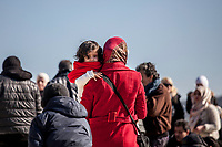 MYTILINI, GREECE - FEBRUARY 09: A woman holds her young daughter after arriving at the Moria refugee camp with dozens of refugees on February 09, 2015 in Mytilini, Greece. After travelling for more than two hours crossing the Aegean sea, refugees are picked up by buses run by UNHCR and transferred to the Moria refugee camp where they have to register their names. As thousands of refugees arrive everyday in Lesvos, queues for registration can take up to two days. In the camp several international organisations provide assistance to the refugees as food, medical assistance, blankets and clothes among other items and services. Photo: © Omar Havana. All Rights Are Reserved