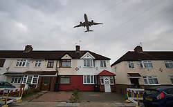 "© Licensed to London News Pictures. 27/10/2016. London, UK. An airliner comes into land over houses near Heathrow Airport. The government has announced that a third runway will be built at the United Kingdom's busiest airport. The Cabinet are divided - with Foreign Secretary Boris Johnson saying that the project is ""undeliverable"". Conservative MP for Richmond Zac Goldsmith has resigned. Photo credit: Peter Macdiarmid/LNP"