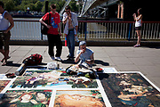 Street artist using chalks and pastels recreates some classical paintings on the pavement for money. A form of artistic busking.