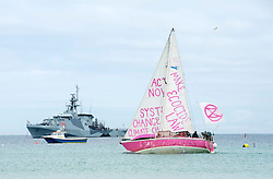 © Licensed to London News Pictures; 11/06/2021; St Ives, Cornwall UK. G7 summit in Cornwall. A pink XR protest yacht passes in front of HMS Tamar in the background at a protest by Extinction Rebellion in St Ives on the first day of the G7 summit. Photo credit: Simon Chapman/LNP.