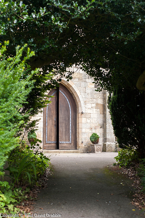 The heavy wooden doors into Saint Oswalds 12th Century Church, Filey through and archway of foliage