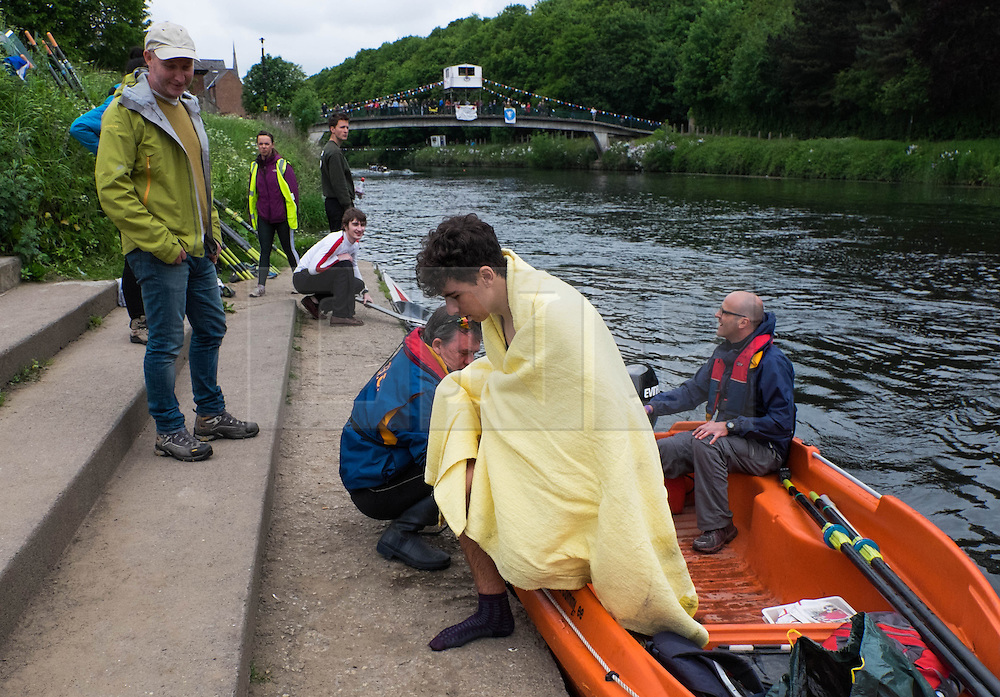 © Licensed to London News Pictures.13/06/15<br /> Durham, England<br /> <br /> A rower who collided with another boat climbs out of a rescue boat during the 182nd Durham Regatta rowing event held on the River Wear. The origins of the regatta date back  to commemorations marking victory at the Battle of Waterloo in 1815. This is the second oldest event of this type in the country and attracts over 2000 competitors from across the country.<br /> <br /> Photo credit : Ian Forsyth/LNP