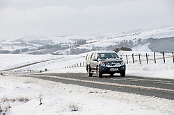 © Licensed to London News Pictures. 14/01/2015. A car travels along the B4520 'Brecon Road' between Brecon and Builth Wells on the Mynydd Epynt range on high land. Snow fell last night in Mid-Wales and cold temperatures have prevented the snow from melting. Builth Wells, Powys , Wales, UK. Photo credit: Graham M. Lawrence/LNP