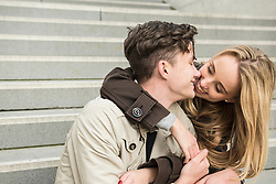 Young couple sitting on stairs and kissing, Munich, Bavaria, Germany