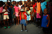 Giovanny Legagneur, 5, acts as if taking a photograph in a camp for displaced people due to Jan.12 earthquake in downtown Port-au-Prince, Haiti, Feb. 5,  2010. (AP Photo/Rodrigo Abd)