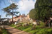Houses overlook gravestones in the historic churchyard of Saint Mary's, Woodbridge, Suffolk, England