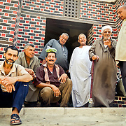 Men gather on the doorstep of an Ottoman era mosque shortly before noon prayers. Rashid, Egypt.