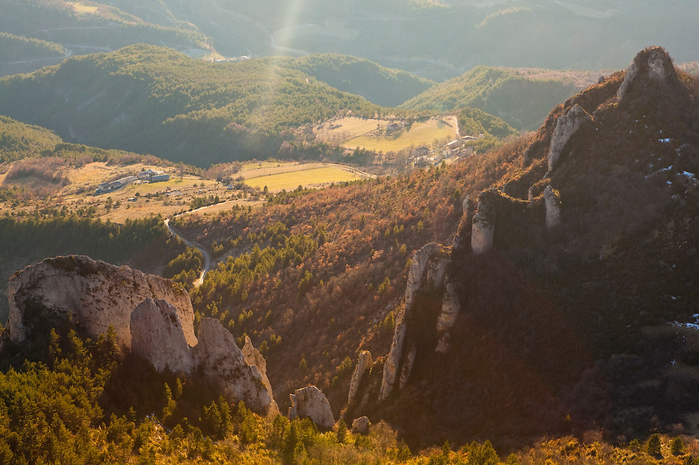 A sun beam illuminates limestone crags and small farms in the Diois, Drôme Valley, France.
