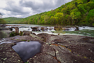 The overcast rain clouds can be seen reflected in a pool of water from a rocky outcrop overlooking the falls of Valley Falls State Park on the Tygart River.