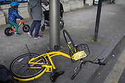 A fallen Ofo dockless hired bike lies on the pavement as a young child scoots past with its mother in Herne Hill, on 26th February 2018, in south London, England.
