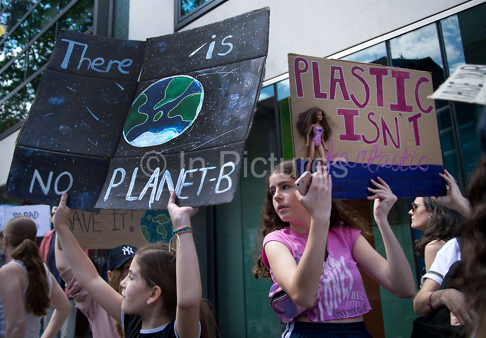 School Climate Strike, London, England, UK. One girl holds a sign with a Barbie doll which says Plastic is not fantastic and another has a sign saying There is No Planet B.