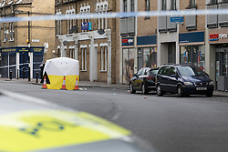 © Licensed to London News Pictures. 03/06/2017. LONDON, UK.  Police officers and a police car at the crime scene cordon in Peckham, near Camberwell in south east London this morning.  A teenage boy, 17 was stabbed to death in Southampton Way near the Tesco Express store. Photo credit: Vickie Flores/LNP