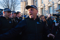 London, March 7th 2015. Following the Climate march through London, masked anarchists and environmental activists clash with police following a breakaway protest at Shell House. PICTURED: A TSG police officer shouts orders as anti-fracking activists and anarchist block the departure of a police van containing one of their colleagues.