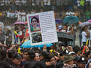 23 JUNE 2016 - MAHACHAI, SAMUT SAKHON, THAILAND:  People hold up a photo of Aung San Suu Kyi while they wait in a driving rainstorm to see her after her visit to the Burmese community in Samut Sakhon, a province south of Bangkok. Tens of thousands of Burmese migrant workers, most employed in the Thai fishing industry, live in Samut Sakhon. Aung San Suu Kyi, the Foreign Minister and State Counsellor for the government of Myanmar (a role similar to that of Prime Minister or a head of government), is on a state visit to Thailand. Even though she and her party won the 2015 elections by a landslide, she is constitutionally prohibited from becoming the President due to a clause in the constitution as her late husband and children are foreign citizens       PHOTO BY JACK KURTZ