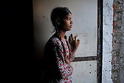 Poonam, 12, is lost in thoughts while standing by the door of her family's newly built home in Oriya Basti, one of the water-contaminated colonies in Bhopal, central India, near the abandoned Union Carbide (now DOW Chemical) industrial complex, site of the infamous '1984 Gas Disaster'.