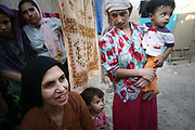 Marzia, 46, at left, and Farida, 33, at right, are the first and the second wives of Noor Agha, 52, with two of 11 children in their house (girls on the left are their relatives), Kabul, Afghanistan, Friday, Aug. 10, 2007. Noor Agha is a renowned kite maker who made kites for the movie makers of the best-selling novel, The Kite Runner, which will be distributed by Dreamworks and Paramount Vantage in Nov. this year. Noor Agha's wives, using their special glue, help him produce enough kites to please the clients' needs. Some of his children can also make their own kites with plastic bags and bamboo sticks. As the Afghan New Year's Day (Nawruz) approaching on March 21, the finger tips of Noor Agha's family got busier for mass production.