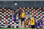 Tranmere Rover's Kaiyne Woolery competes for a high ball with Newport County's Mickey Demetriou (28) during the EFL Sky Bet League 2 match between Newport County and Tranmere Rovers at Rodney Parade, Newport, Wales on 17 October 2020.
