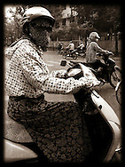 Women cover themselves with sun coats and masks as they drive in Hanoi, Vietnam, Southeast Asia
