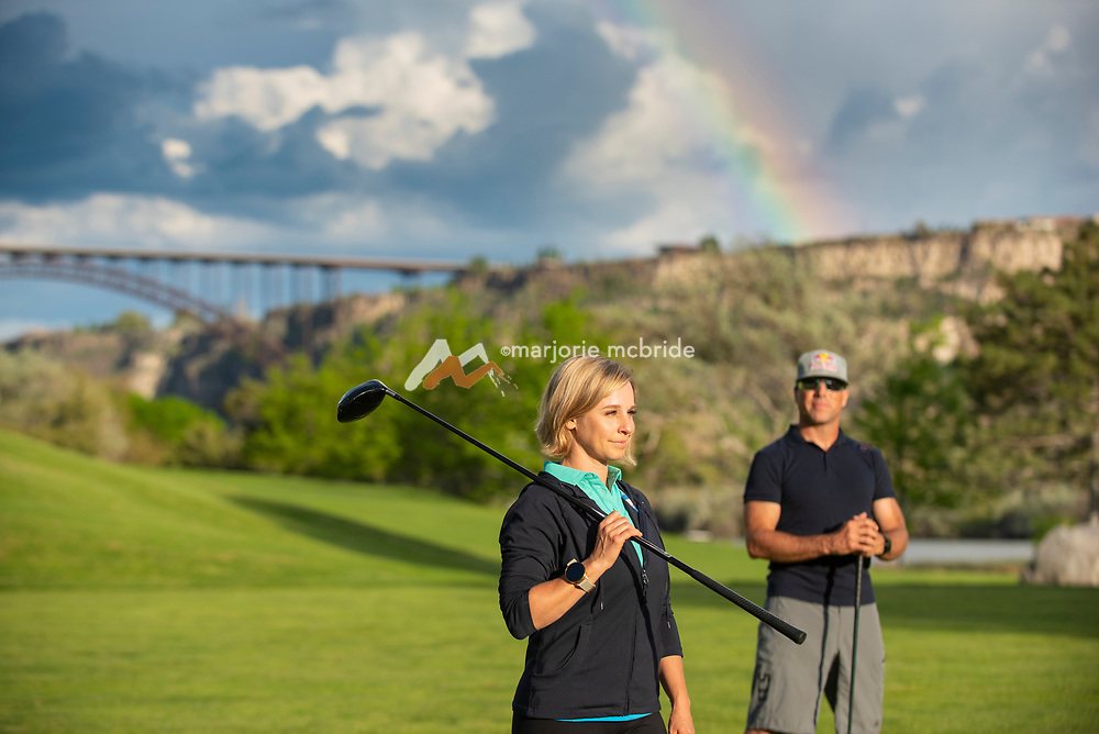 Couple golfing during spring with rainbow overhead while man watches woman with club over her shoulder looking down the course at Blue Lakes Country Club, Twin Falls, Idaho.