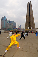 Chinese people practicing tai chi in the early morning in Huangpu Park (with the Monument to the People's Heroes in the background), Shanghai, China