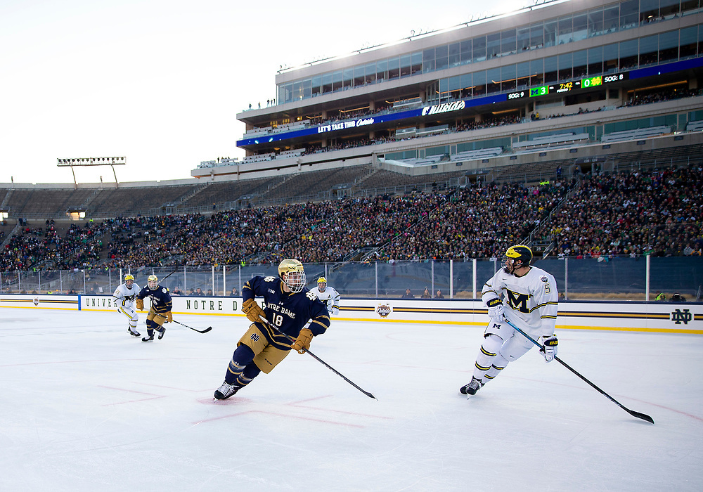 January 05, 2019:  A general view as Michigan defenseman Griffin Luce (5) skates with the puck and Notre Dame forward Graham Slaggert (18) forechecks during NCAA Hockey game action between the Michigan Wolverines and the Notre Dame Fighting Irish at Notre Dame Stadium in South Bend, Indiana.  Michigan defeated Notre Dame 4-2.  John Mersits/CSM