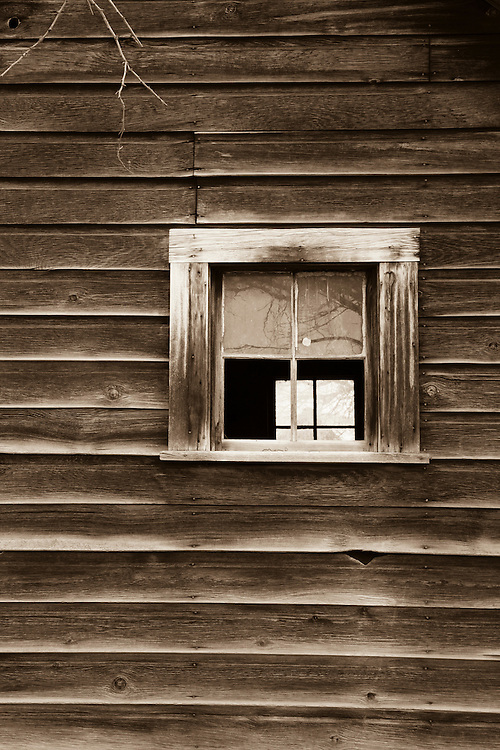 The window of an abandoned homestead looks out on the high desert landscape of central Oregon.