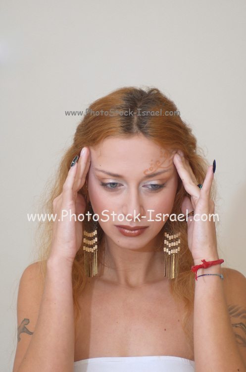 A blond model Massaging her head to relive the Pain and tension