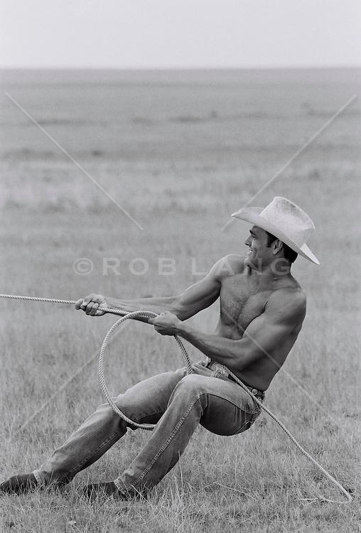 Male cowboy pulling lasso in field (B&W)