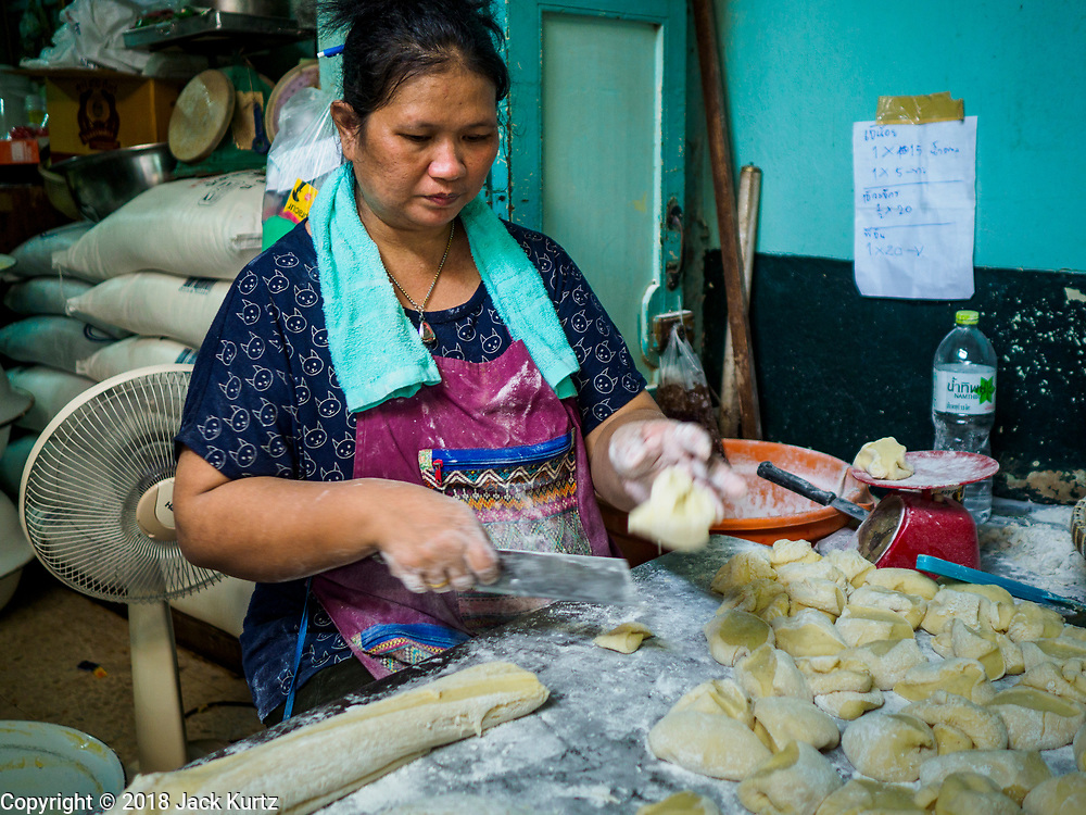"""12 FEBRUARY 2018 - BANGKOK, THAILAND: A woman cuts dough for steamed buns in a home that makes steamed Chinese buns, called """"bao"""" in the Chinatown neighborhood of Bangkok. Bao are eaten at midnight on the Lunar New Year and served to guests during New Year's entertaining. Lunar New Year, also called Tet or Chinese New Year, is 16 February this year. The coming year will be the Year of the Dog. Thailand has a large Chinese community and Lunar New Year is widely celebrated in Thailand, especially in Bangkok and large cities with significant Chinese communities.    PHOTO BY JACK KURTZ"""