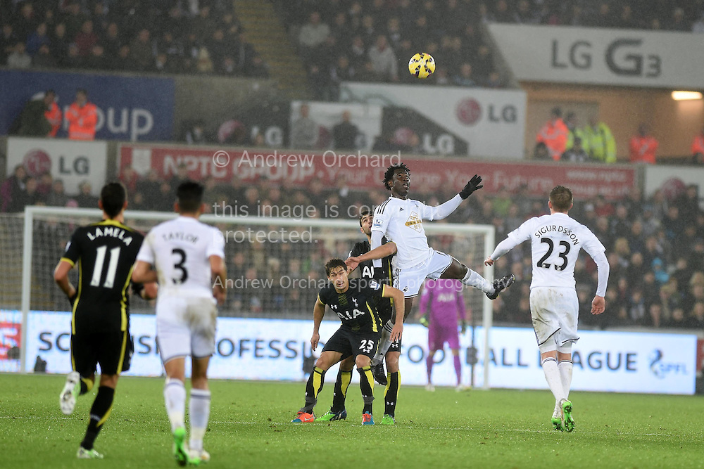 Swansea city's Wilfried Bony wins a header. Barclays Premier League match, Swansea city v Tottenham Hotspur at the Liberty Stadium in Swansea, South Wales on Sunday 14th December 2014<br /> pic by Andrew Orchard, Andrew Orchard sports photography.