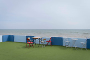 A landscape of chairs and tables against a wall of an outdoor seafront cafe that was once a part of the St Leonards Bathing pool opened 1933, on 3rd May 2021, in St Leonards, Sussex, England.