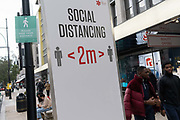 Londoners pass beneath a social distancing sign that urges the public to keep 2 metres apart on Oxford Street during the second (Autumn) wave of the Coronavirus pandemic, on 8th October, 2020, in London, England. (Richard Baker / In Pictures via Getty Images)
