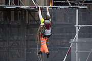 An activist from the group Action for Climate Truth and Reparations (ACTR) climbs scaffolding to hang an open letter to the UK people from Africans Rising For Justice, Peace and Dignity from the Houses of Parliament on 12 November 2020 in London, United Kingdom. The letter, which launches Africans Rising's ReRight History campaign, contains a plea to the UK people to start making amends for the harm caused by slavery and colonialism.
