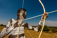 Kara tribe boy with chalk body painting shooting a bow and arrow, Omo Valley, Ethiopia.