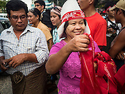 09 NOVEMBER 2015 - YANGON, MYANMAR:  A woman walks down the street selling NLD merchandise at NLD headquarters Monday evenng. Thousands of National League for Democracy (NLD) supporters gathered at NLD headquarters on Shwegondaing Road in central Yangon to celebrate their apparent landslide victory in Myanmar's national elections that took place Sunday. The announcement of official results was delayed repeatedly Monday, but early reports are that the NLD did very well against the incumbent USDP.    PHOTO BY JACK KURTZ