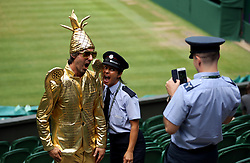 Fan Chris Fava, dressed as the Wimbledon Men's trophy poses for a photo with a member of London fire brigade on centre court on day seven of the Wimbledon Championships at the All England Lawn Tennis and Croquet Club, Wimbledon.