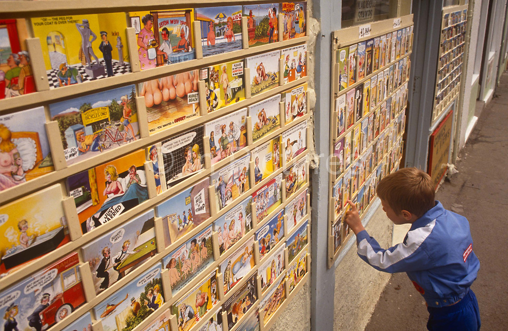 A young boy looks carefully at the many saucy postcards on sale outside a seaside shop, on 19th July 1993, in Scarborough, North Yorkshire, England. Telling jokes to send back to friends and family, they using cartoon characters of buxom women, hen-pecked husbands or sexually-frustrated young men, the humour is bawdy and cheeky - the epitome of seaside holiday kitsch. The best-known saucy seaside postcards were created by Bamforths founded 1870 and despite the decline in popularity of postcards that are overtly tacky, postcards continue to be a significant economic and cultural aspect of British seaside tourism. In the 1950s, Bamforth postcards were among the most popular of the 18 million items purchased at British resorts.