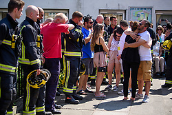 © Licensed to London News Pictures. 19/06/2017. London, UK. Family of fire victim Jessica Urbano embrace each other as they join firefighters at a minutes silence held near the scene of the Grenfell tower block fire. The blaze engulfed the 27-storey building killing dozens - with 34 people still in hospital, many of whom are in critical condition. Photo credit: Ben Cawthra/LNP