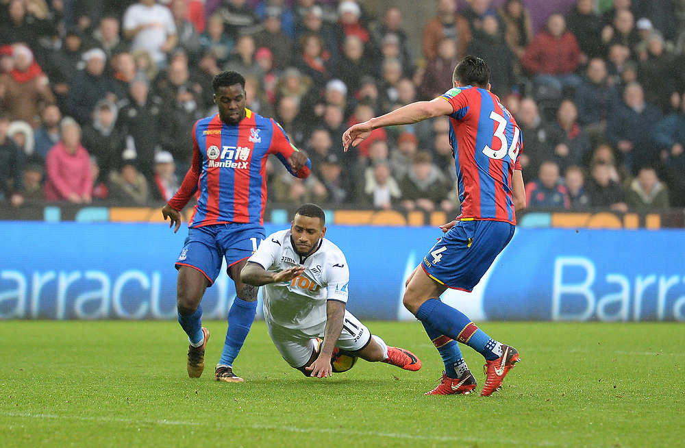 Swansea City's Luciano Narsingh goes down under the challenge of Crystal Palace's Jeffrey Schlupp<br /> <br /> Photographer Ian Cook/CameraSport<br /> <br /> The Premier League - Swansea City v Crystal Palace - Saturday 23rd December 2017 - Liberty Stadium - Swansea<br /> <br /> World Copyright © 2017 CameraSport. All rights reserved. 43 Linden Ave. Countesthorpe. Leicester. England. LE8 5PG - Tel: +44 (0) 116 277 4147 - admin@camerasport.com - www.camerasport.com