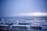 """The town of Iqaluit, Nunavut Territory, Canada after a light snowfall in early October. Iqaluit, with a population of 6,000, is the largest community in Nunavut as well as the capital city. It is located in the southeast part of Baffin Island. Formerly known as Frobisher Bay, the town is at the mouth of the bay of that name, overlooking Koojesse Inlet. """"Iqaluit"""" means 'place of many fish'."""