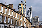 New housing tower blocks dominating the skyline above old low rise traditional houses at Elephant and Castle on 5th March 2021 in London, England, United Kingdom. Elephant and Castle is a fast-changing area with modern developments, some of which is aimed to be affordable housing, while nearby some social housing remains.