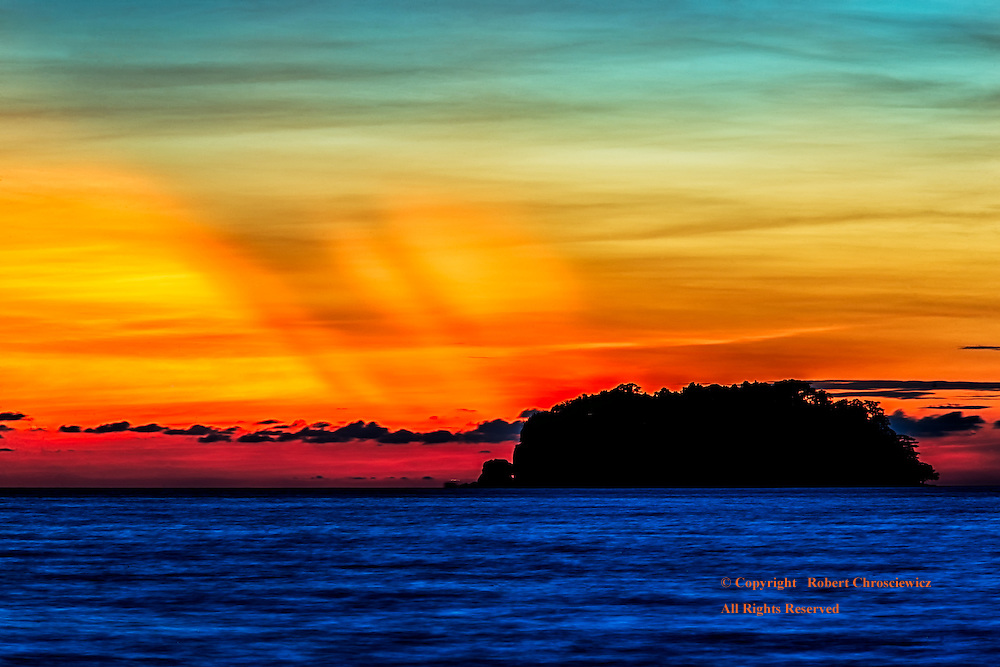 Radiant Rays: Radiant red rays slash the sky at sunset, over a tranquil ocean and a silhouetted island, off Lonely Beach - Ko Chang Thailand.