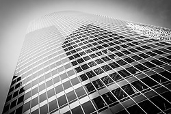 Black and white Chicago curved glass office building skyscraper looking upward toward the sky.