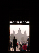 Tourists in the early morning head to the spires of Angkor Wat at Angkor, Siem Reap Province, Cambodia
