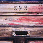 Old wooden door numbered 928 and mail slot
