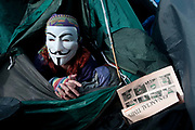 Occupy London Stock Exchange 29.10.2011.Protester wearing Guy Fawkes mask reading The Financial Times in her tent.