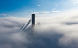The top of a tower of the Queensferry Crossing bridge manages to emerge above heavy fog over the Firth of Forth today, North Queensferry, Scotland, UK