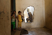 Sunni house on the front line between the Sunni neighborhood Bab al-Tebbaneh and Alawite Jabal Mohsen district. The hole in the wall allows people to move around the neighborhood without venturing into the street, thats is made ??dangerous by snipers. Tripoli, Lebanon..Maison sunnite sur la ligne de front entre le quartier sunnite Bab al-Tebbaneh et le quartier alaouite Jabal Mohsen. Le trou dans le mur permet aux habitants se déplacer dans le quartier sans s'aventurer dans la rue, rendu dangereuse par des snipers. Tripoli, Liban